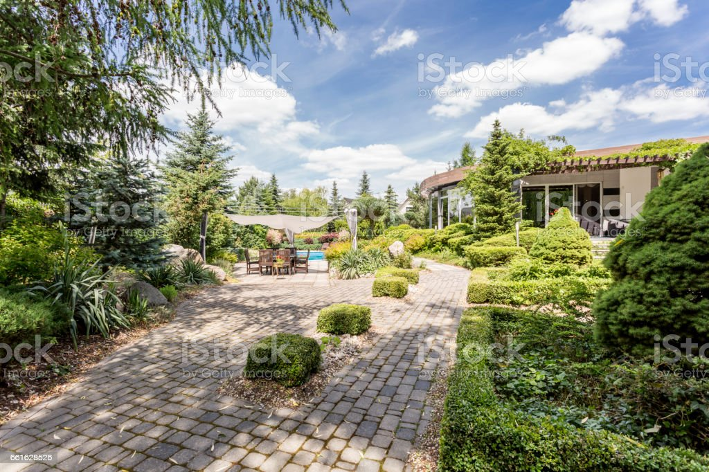 Elegant garden with the paved path stock photo