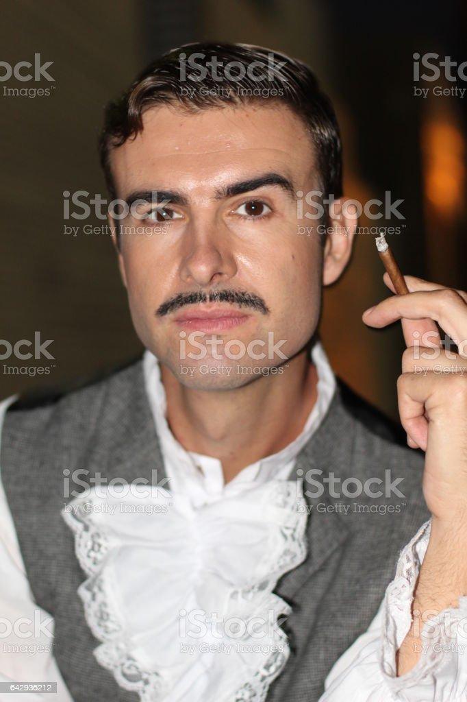 Elegant gentleman holding a cigar. Victorian Era stock photo