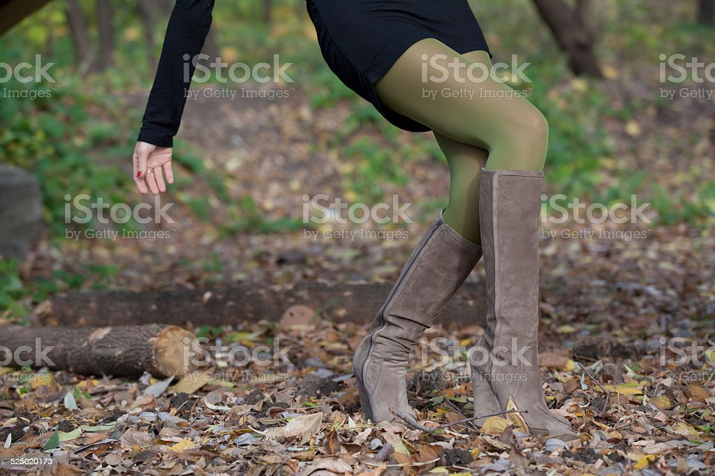 Elegant girl in suede boots walking in the woods stock photo