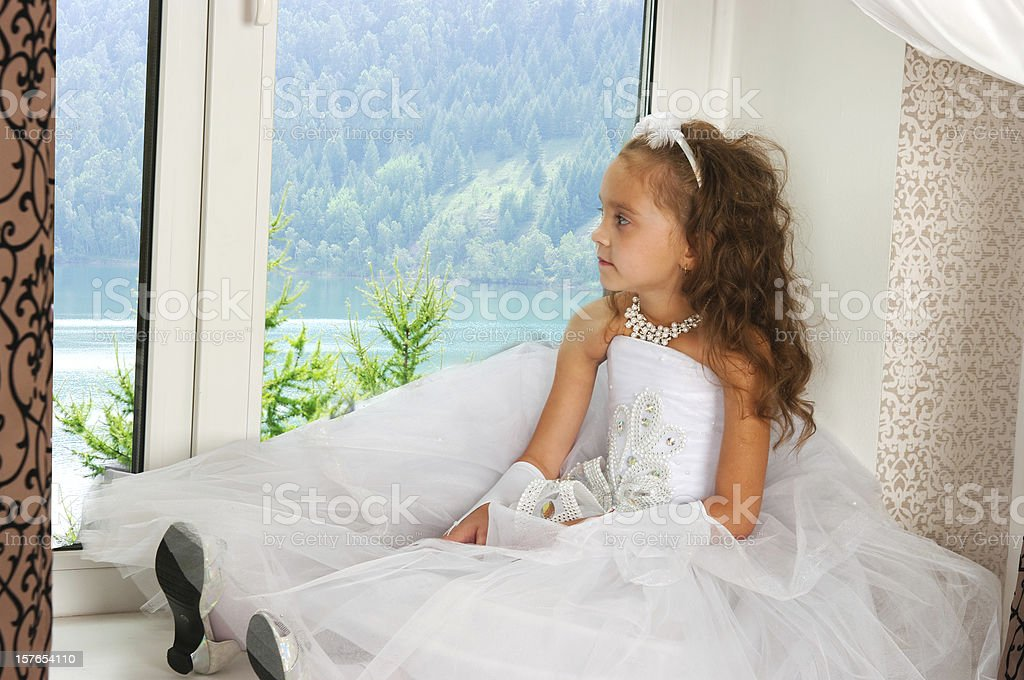 elegant girl in white dress sits on window sill royalty-free stock photo