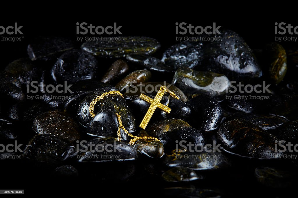 Elegant Gold Cross Pendant on Black Wet Stones stock photo
