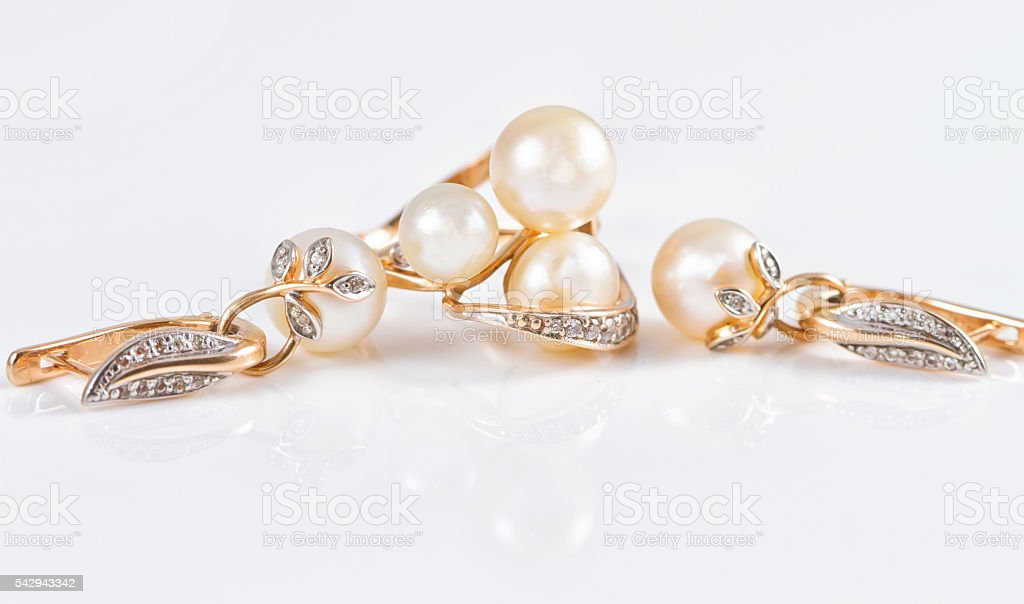 Elegant gold rings and gold earrings with pearls stock photo