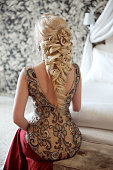 Elegant hairstyle. Beautiful blond woman in fashion red dress