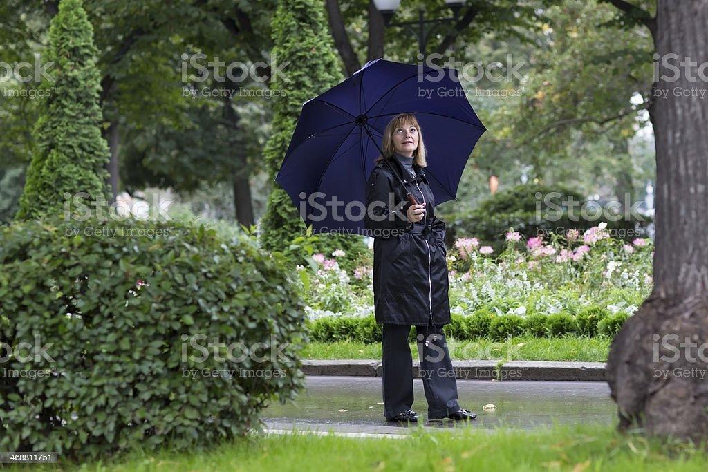 Elegant lady walking in a beautiful park under umbrella royalty-free stock photo