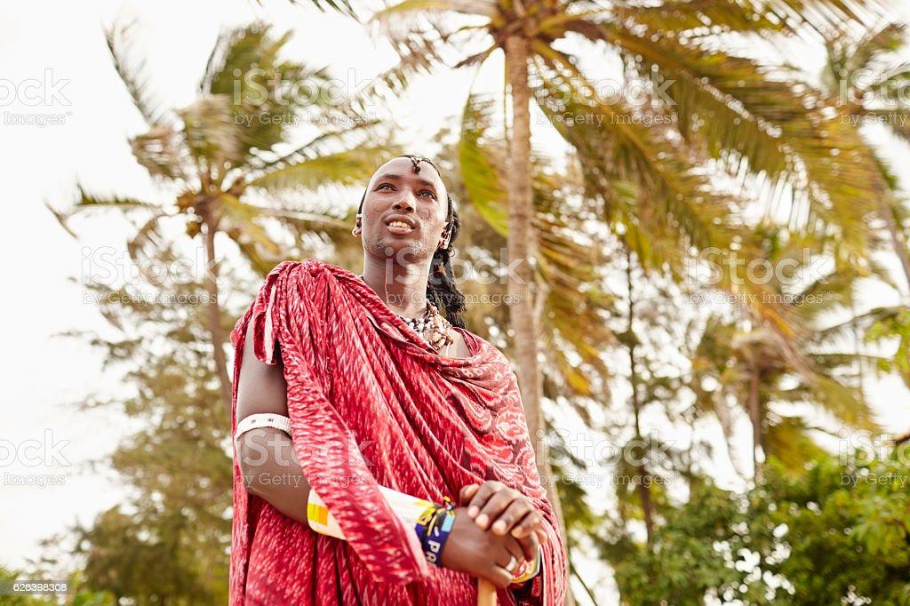 Elegant Maasai man standing under Zanzibars palm trees. stock photo