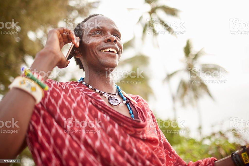 Elegant Maasai man using a smartphone. stock photo