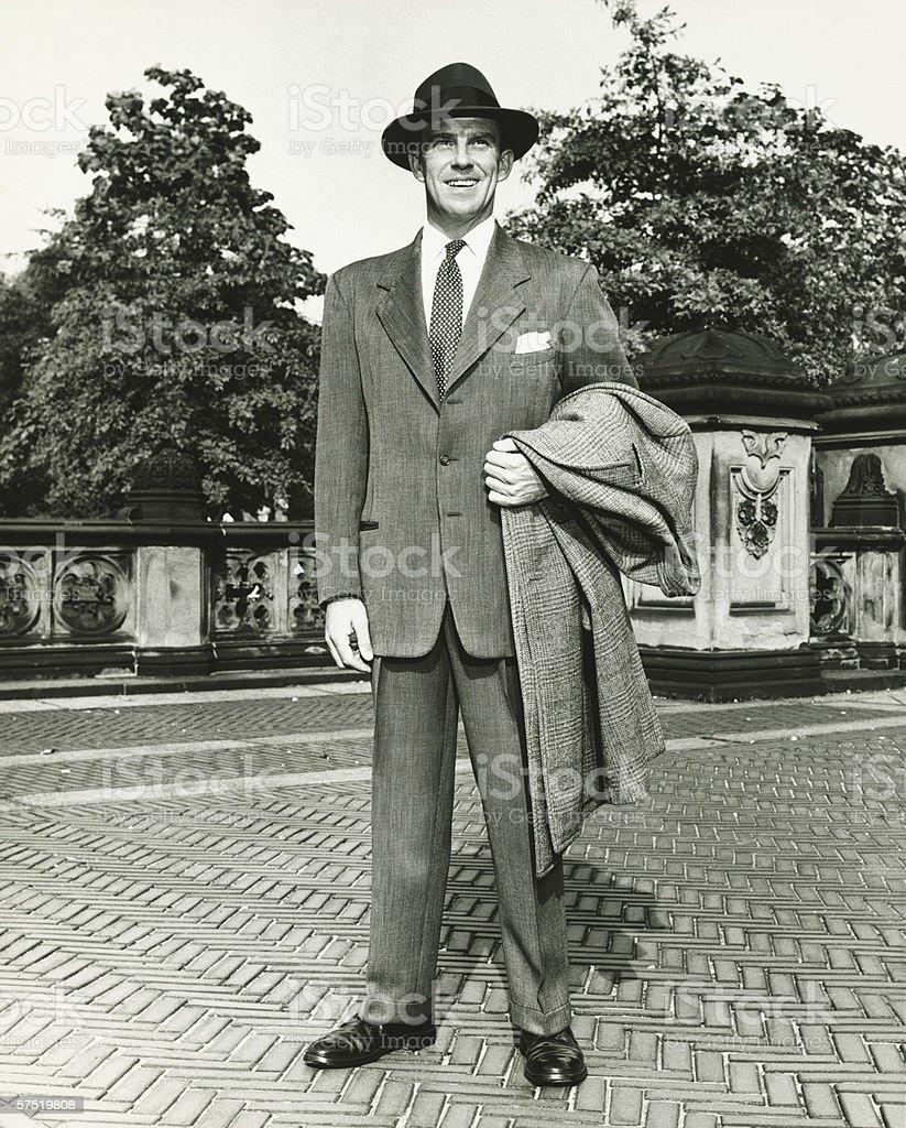Elegant man carrying overcoat courtyard, (B&W), royalty-free stock photo