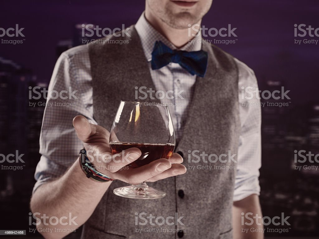Elegant man holding brandy snifter stock photo