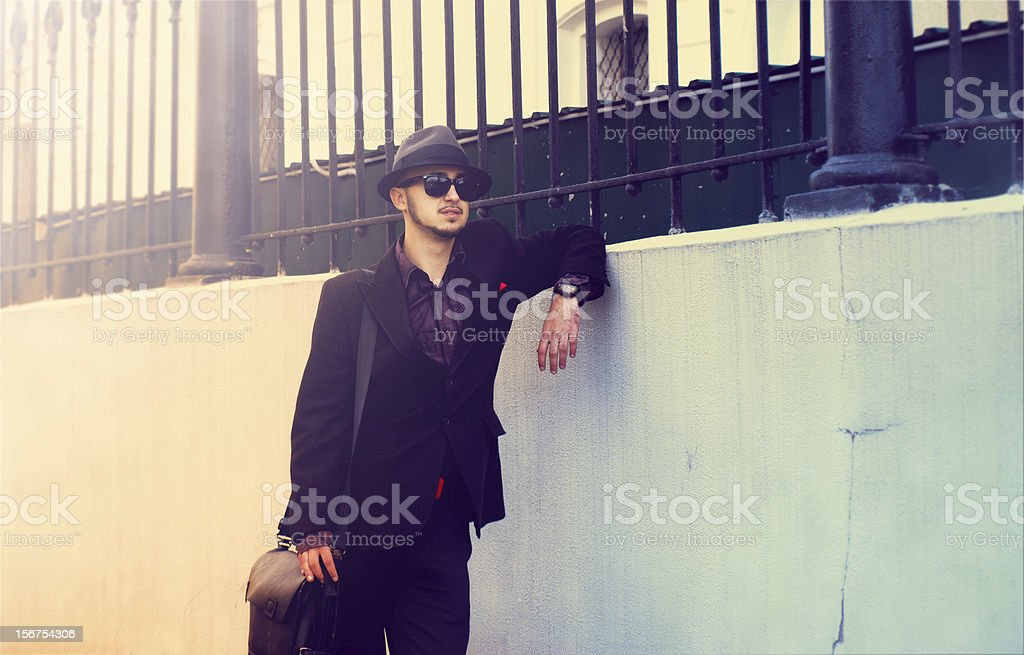 Elegant man in a hat standing near the wall royalty-free stock photo