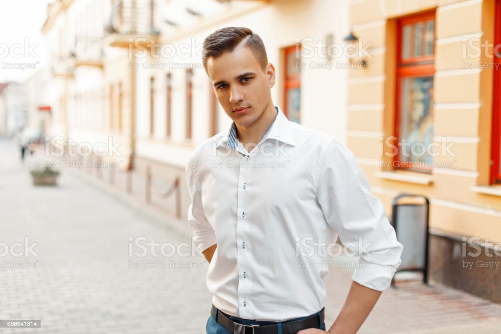 Elegant man in a white shirt in the city stock photo