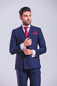 elegant man in suit looking away while unbuttoning shirt