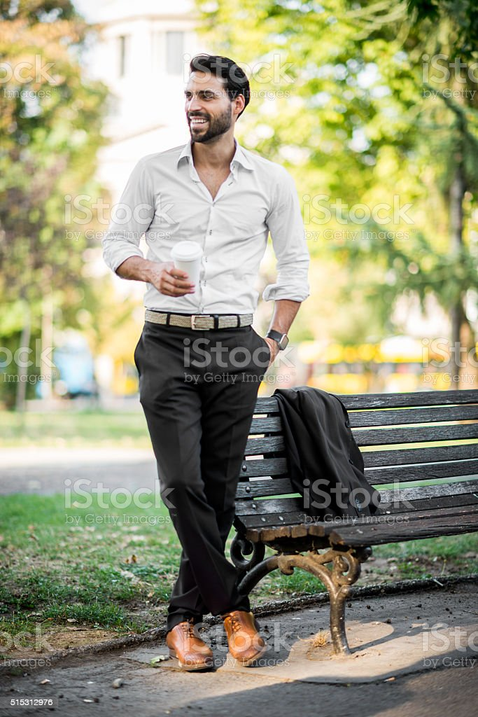 Elegant man in the park drinking coffee stock photo