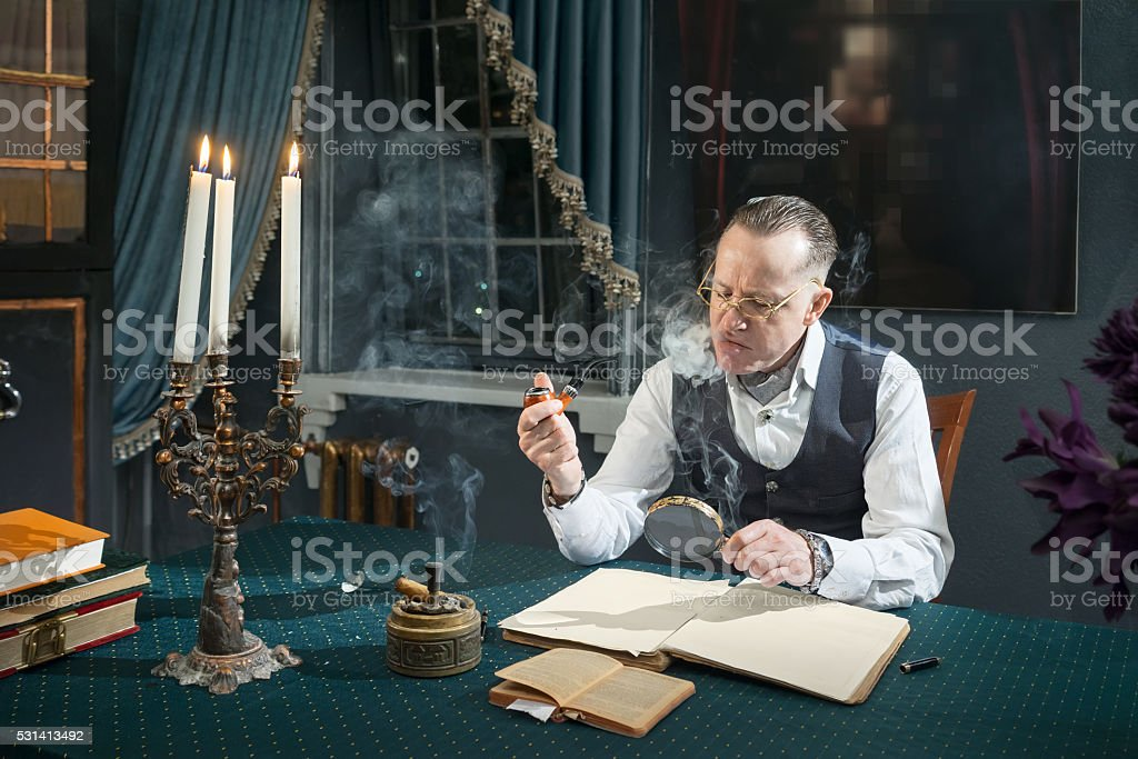 Elegant man looks through a magnifier in book stock photo