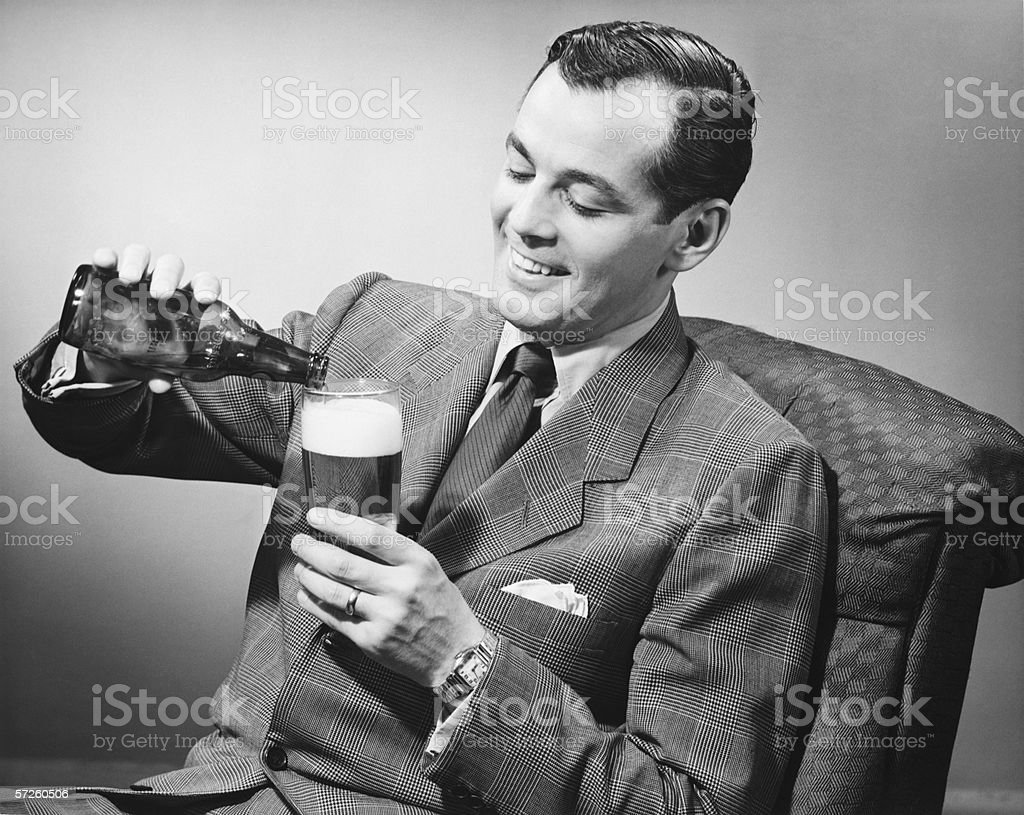 Elegant man pouring beer from bottle into glass, (B&W) stock photo