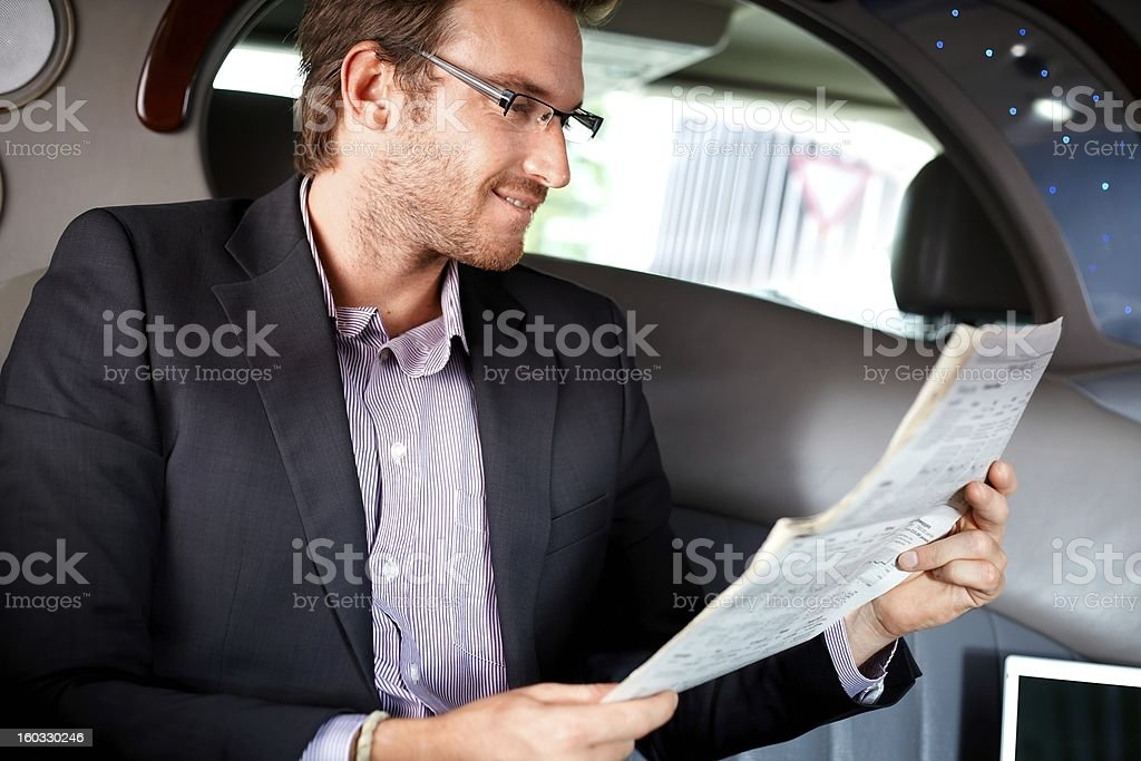Elegant man reading papers in luxury car royalty-free stock photo