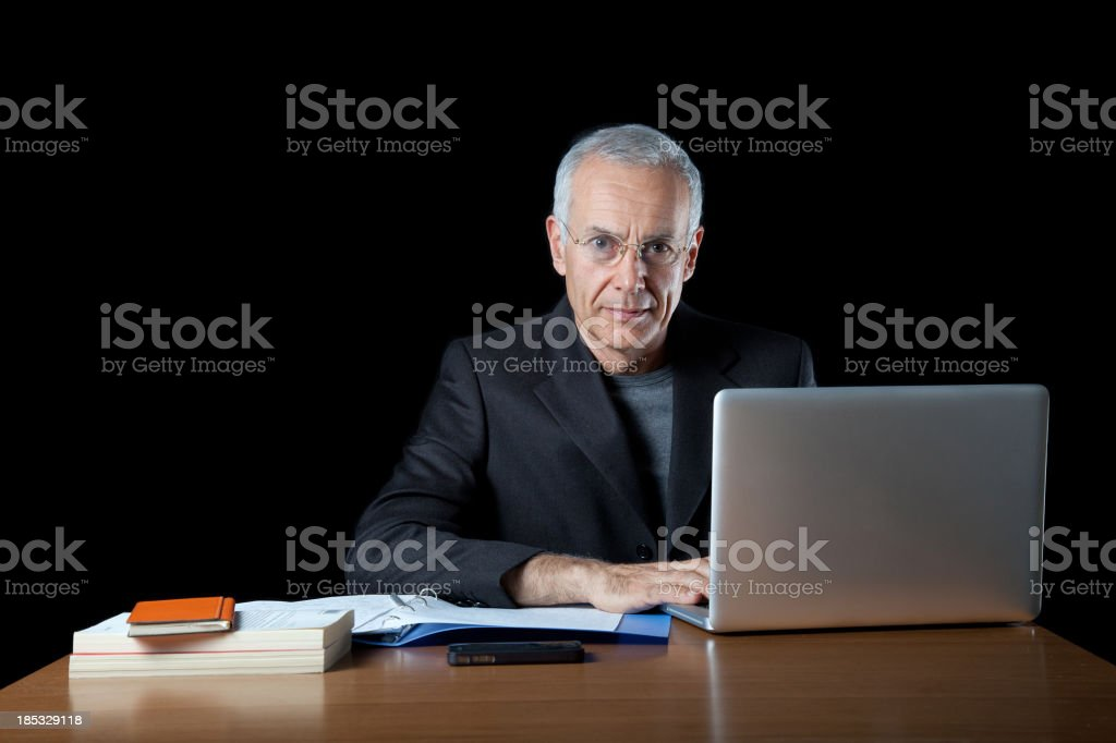 Elegant man seated at desk with laptop stock photo