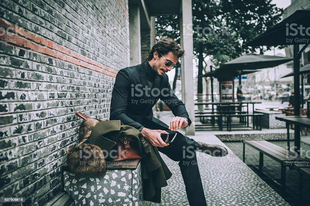 Elegant man sitting on bench stock photo