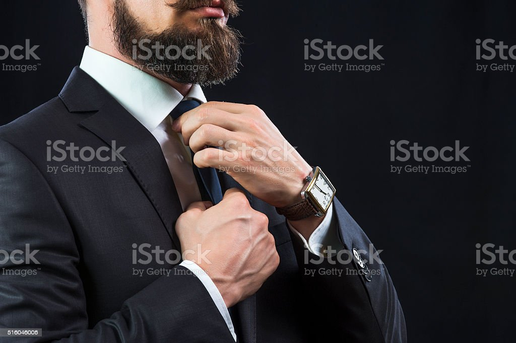 Elegant man tying up his tie stock photo