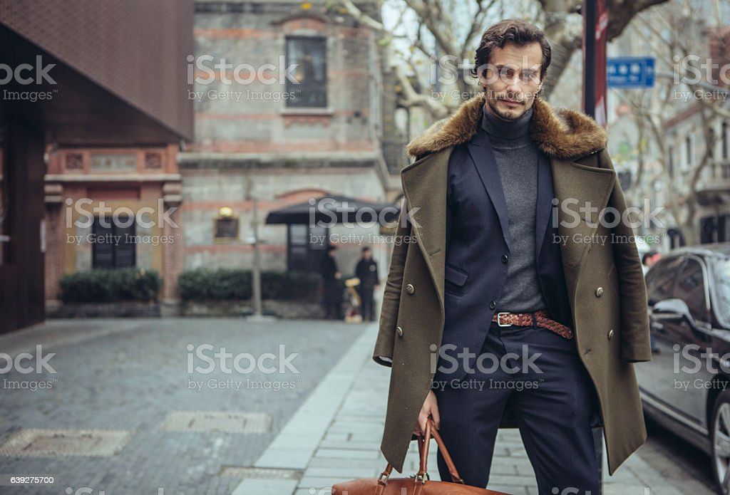 Elegant man with a travel bag stock photo