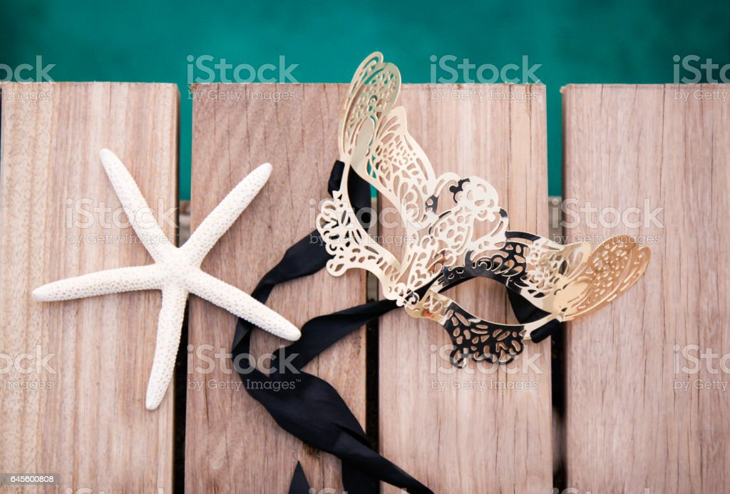 Elegant Mask and Starfish by the sea stock photo