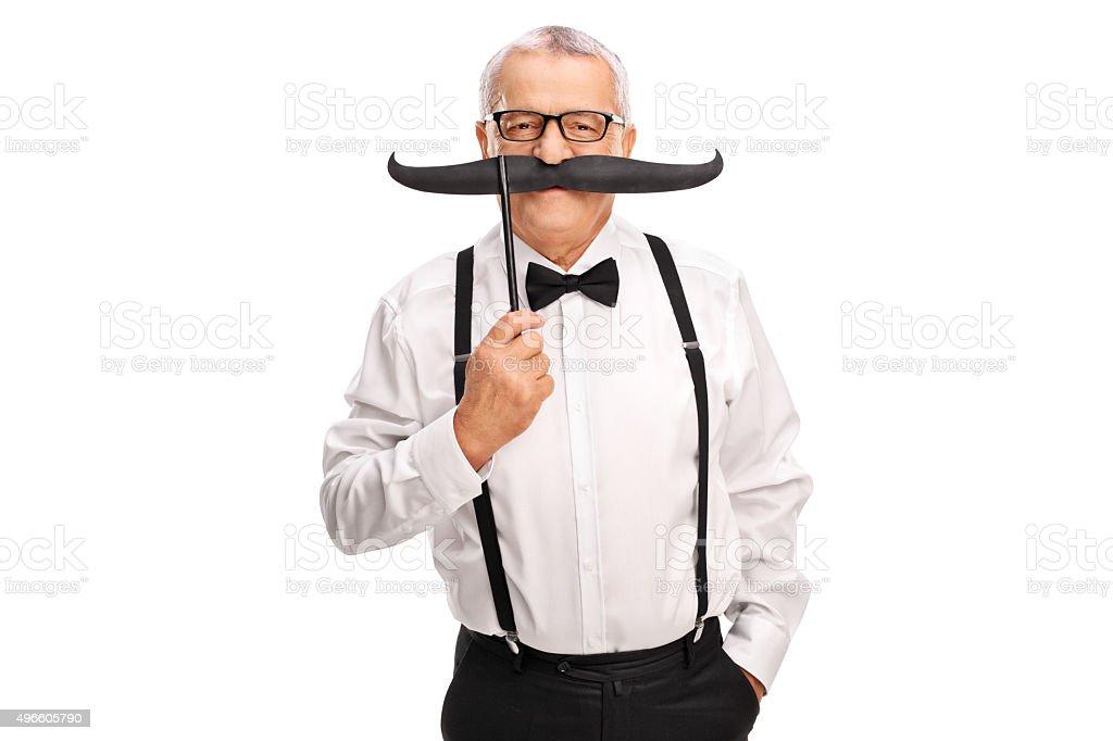 Elegant mature man holding a fake mustache stock photo
