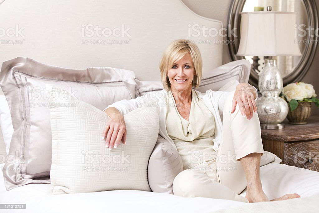 Elegant mature woman is resting on a bed. royalty-free stock photo