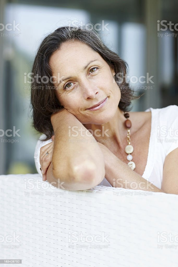 Elegant mature woman relaxing on sofa royalty-free stock photo
