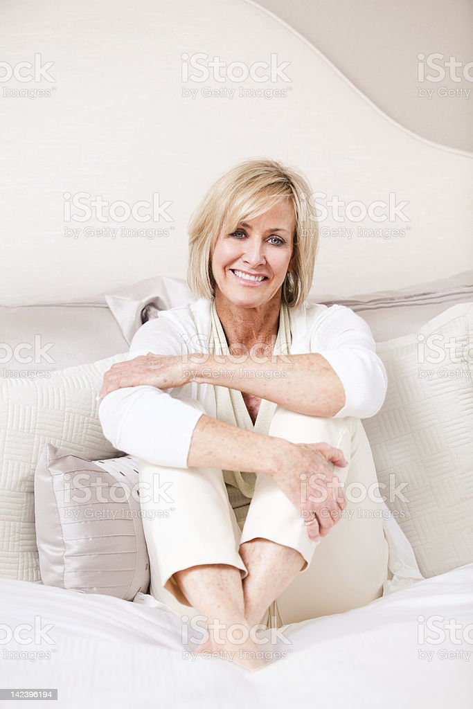 Elegant mature woman sitting with her arms and legs crossed stock photo