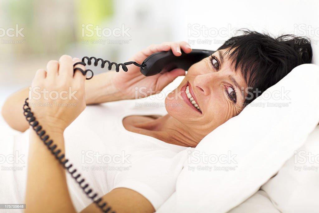 elegant middle aged woman talking on landline phone royalty-free stock photo