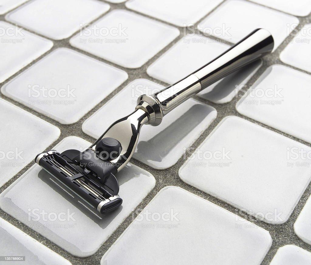 Elegant, modern razor on bathroom tile surface royalty-free stock photo