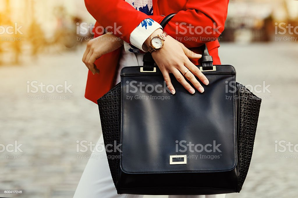 Elegant outfit. Close up. Black leather bag handbag in hands stock photo