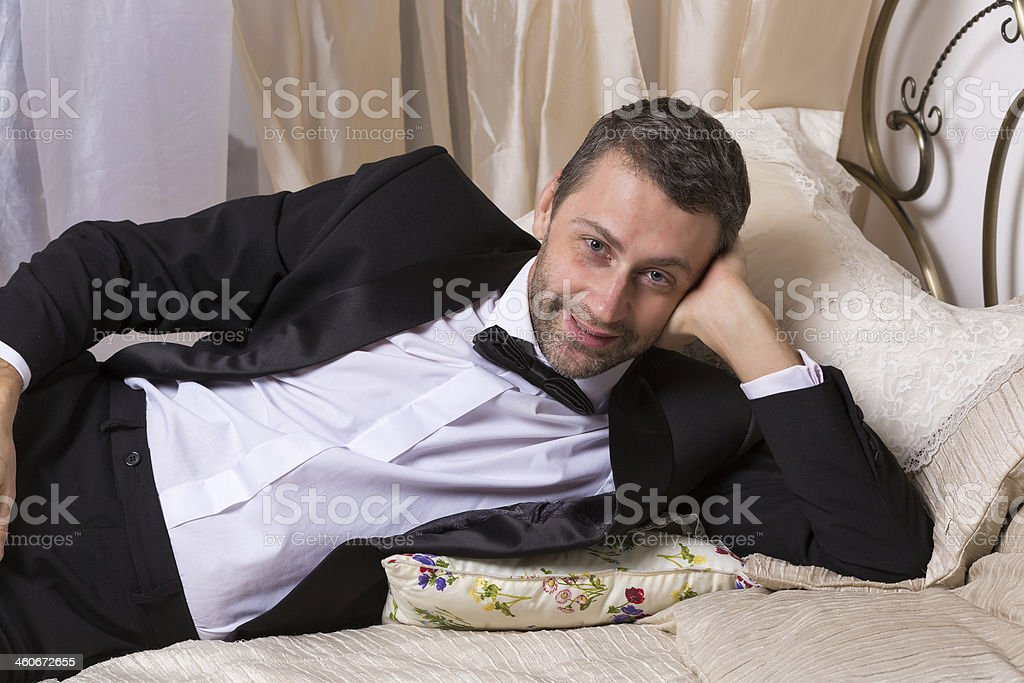 Elegant playboy reclining on a bed stock photo