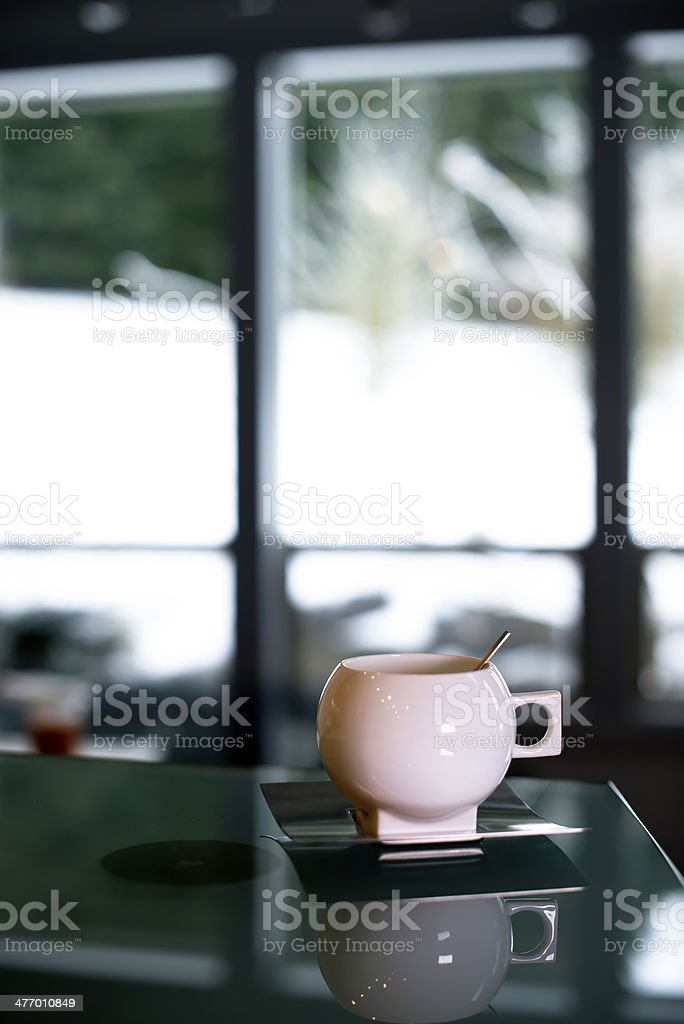 Elegant porcelain cup with stainless steel spoon and saucer royalty-free stock photo