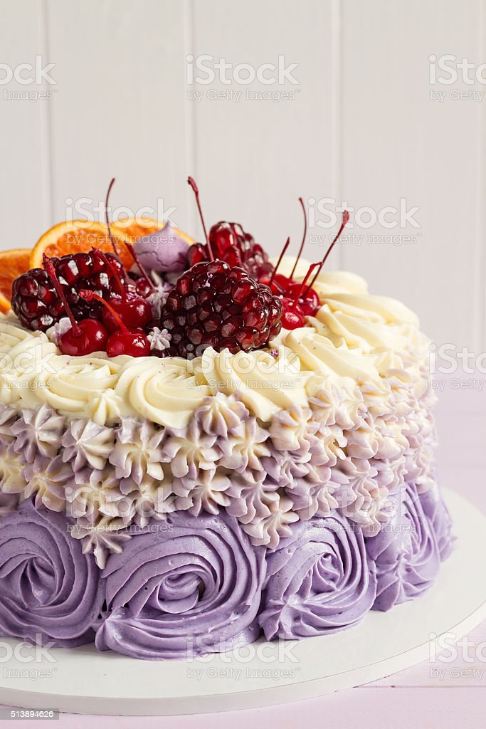 Elegant purple rosette cake decorated with fruit stock photo