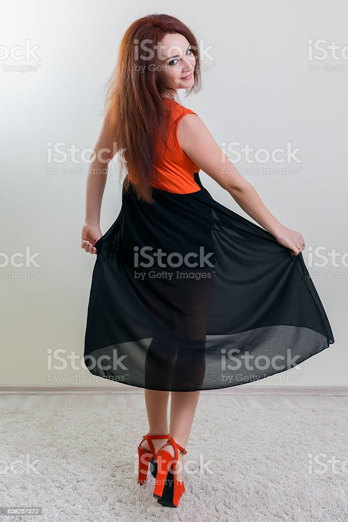 Elegant red haired woman posing looking at camera over shoulder stock photo