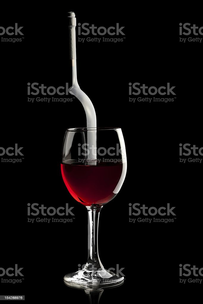 Elegant red wineglass and a wine bottles in black background royalty-free stock photo