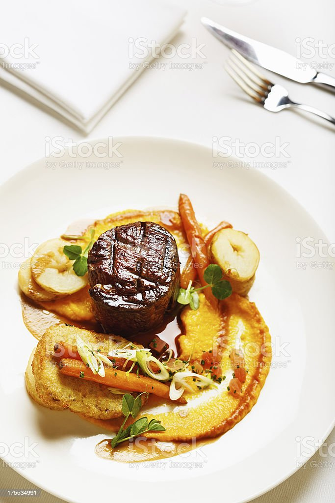 Elegant restaurant serving of filet mignon with vegetable accompaniments stock photo
