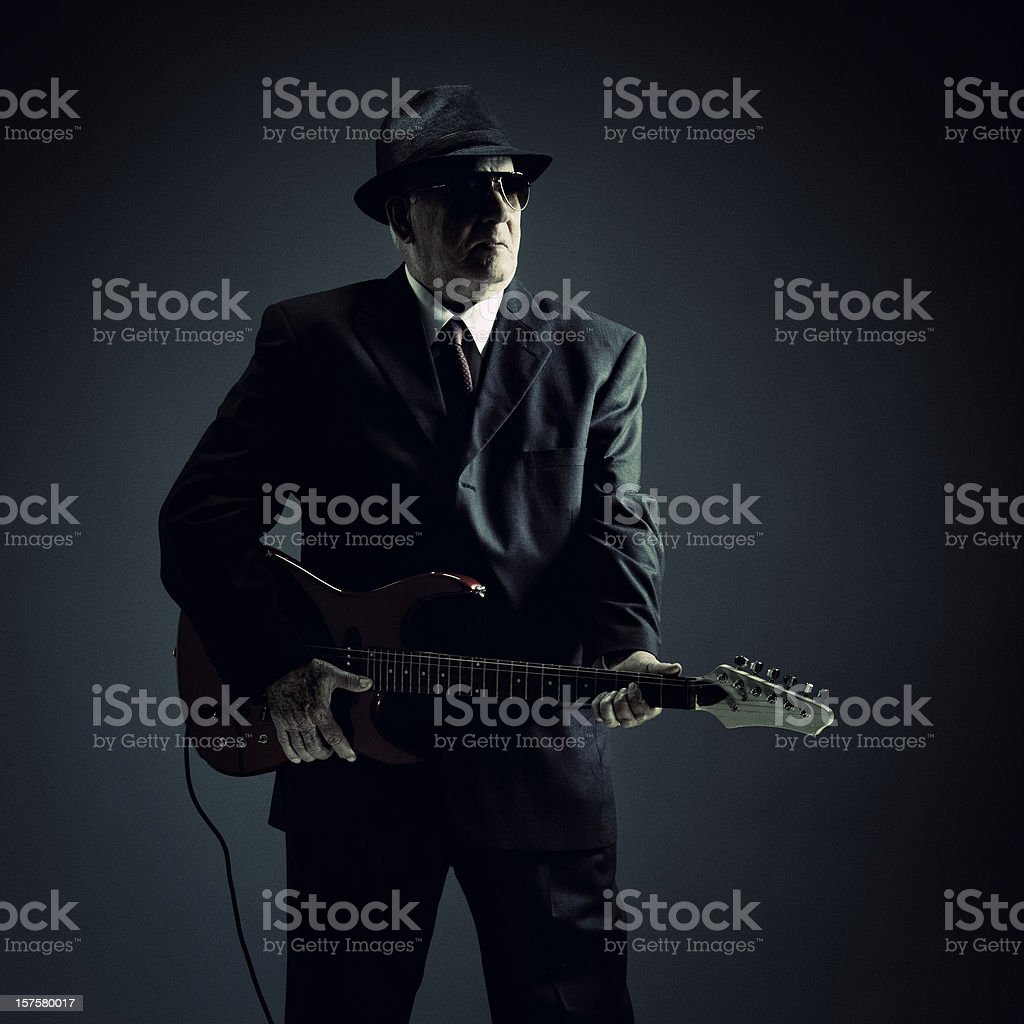 elegant senior playing an electric guitar stock photo