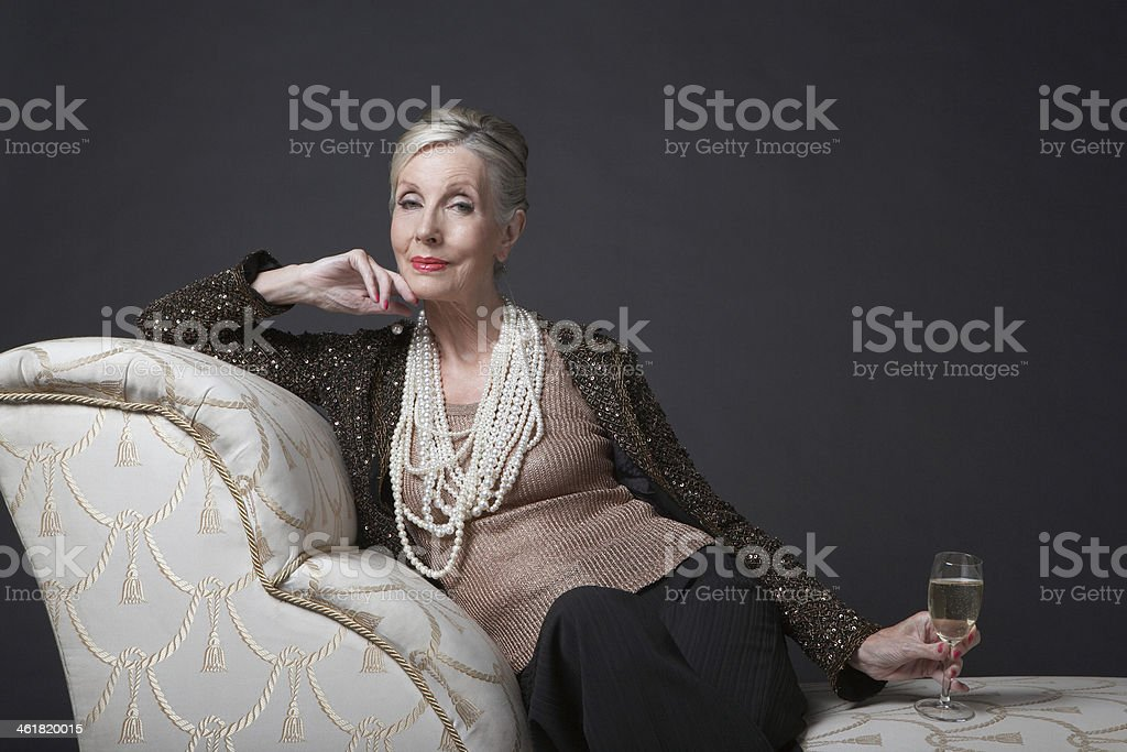 Elegant Senior Woman On Chaise Lounge With Champagne stock photo