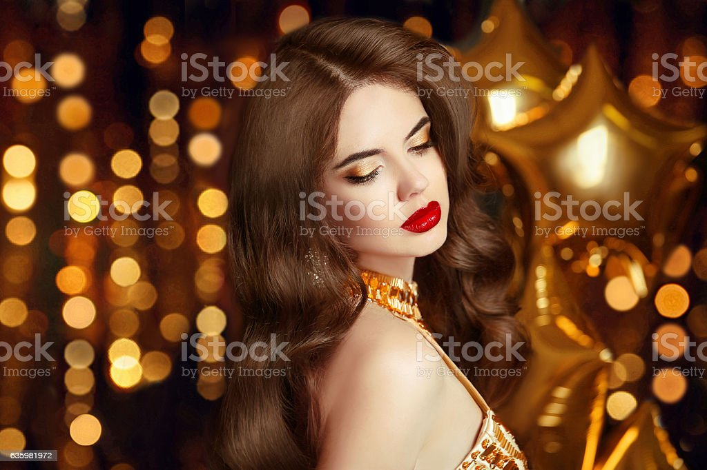 Elegant sexy girl portrait in gold. Makeup. Fashion brunette stock photo
