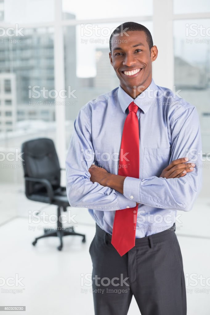 Elegant smiling Afro businessman standing in office stock photo
