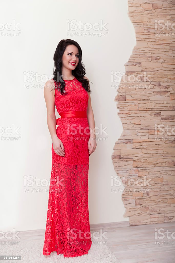 Elegant smiling woman in red openwork dress posing near wall stock photo