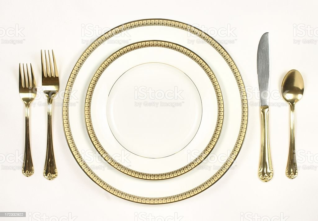 Elegant Table Setting with white and gold plates and silverware stock photo