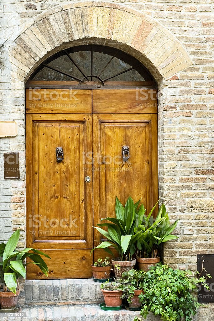 Elegant Tuscany door entrance with plants on doorsteps royalty-free stock photo