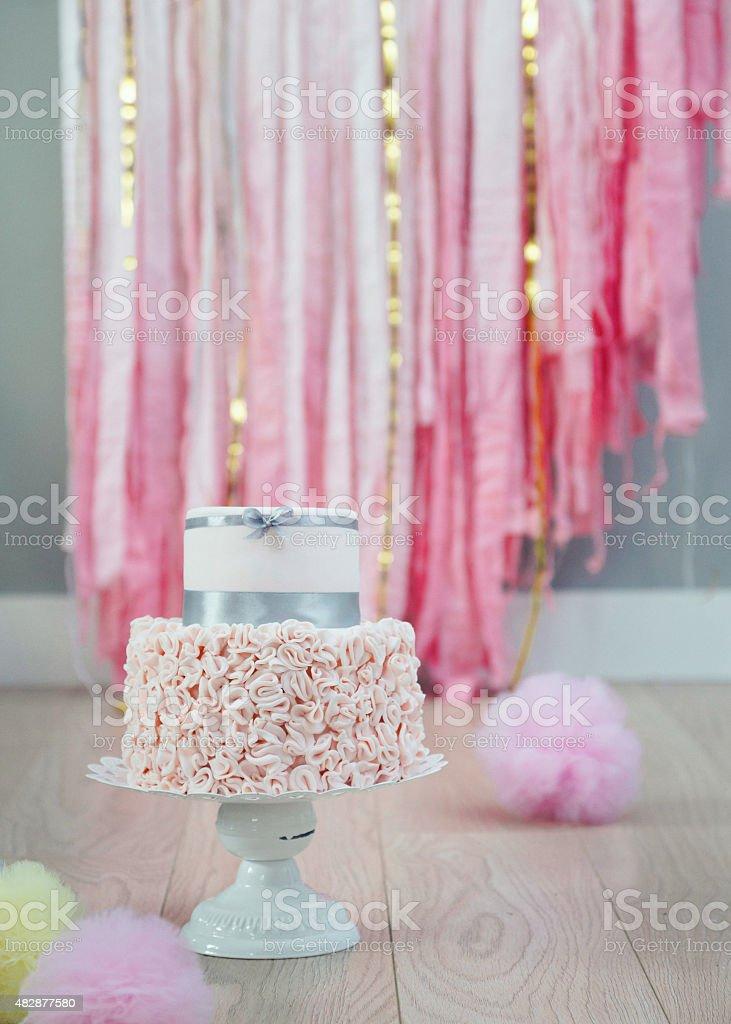 Elegant two-tier birthday or wedding cake with ruffled fondant bottom stock photo