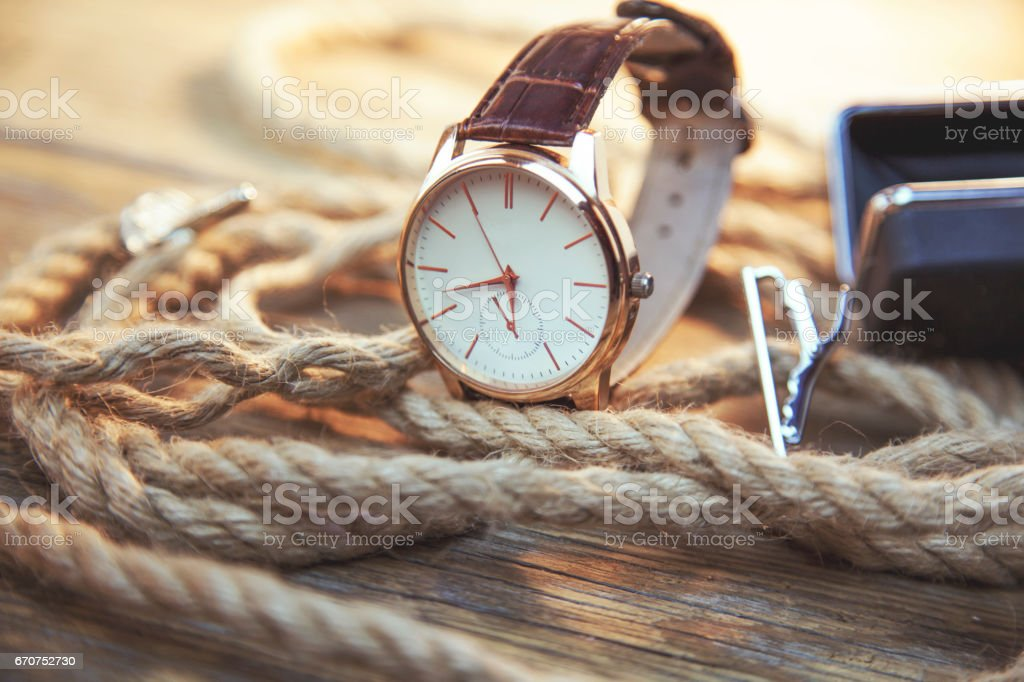elegant  watch and rope on wooden background stock photo