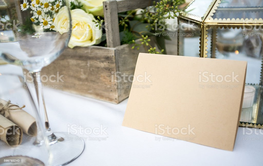 Elegant white dining tables with flowers and blank paper sign stock photo