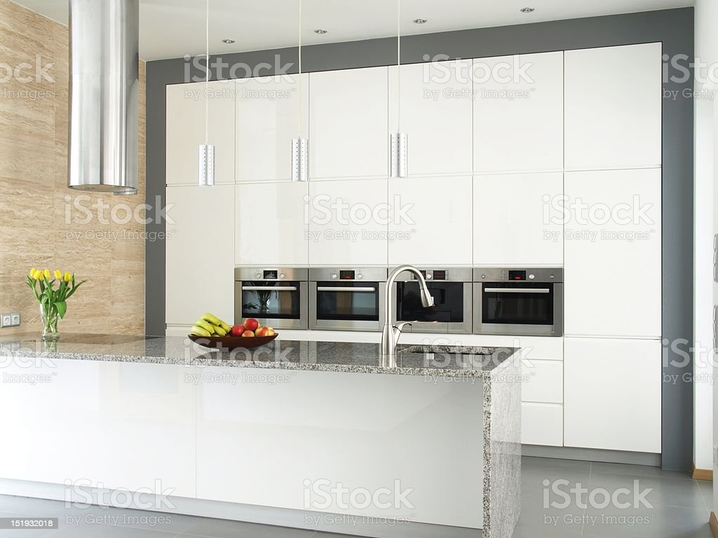 Elegant white kitchen with travertine stone wall stock photo