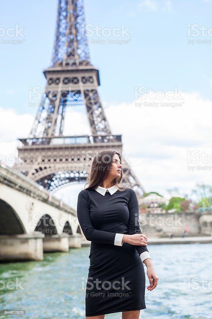 Elegant Woman By The Riverside Near The Eiffel Tower stock photo