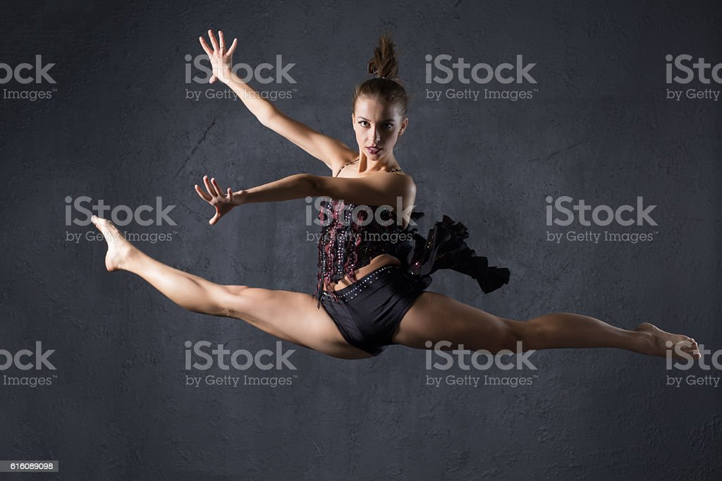 Elegant woman dance in dark studio stock photo